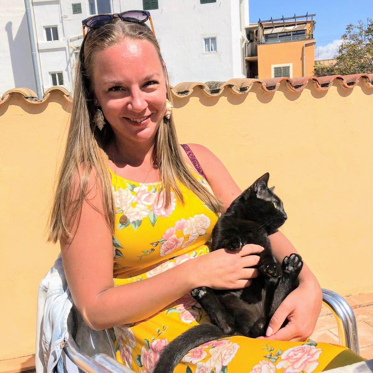 Marika Mayor istuu kesämekossaan kissa sylissä