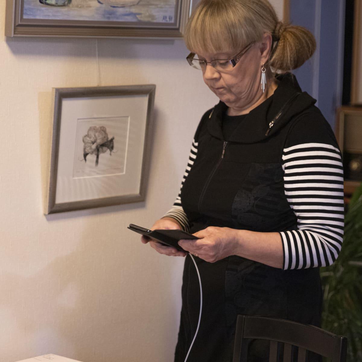 Kirsti Sandell tutkii matkapuhelintaan.