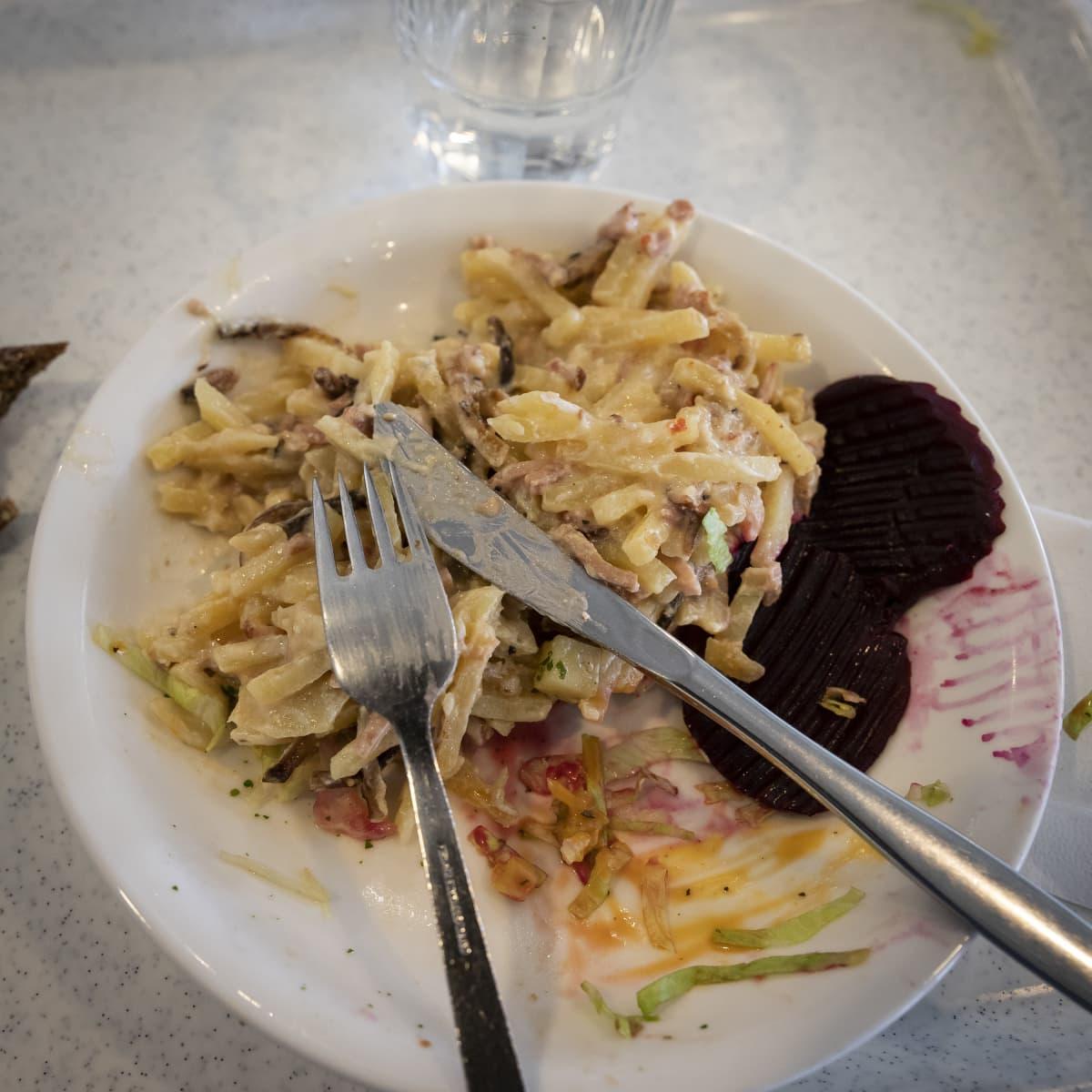 Veitsi, haarukka ja kinkkukiusausta lautasella.