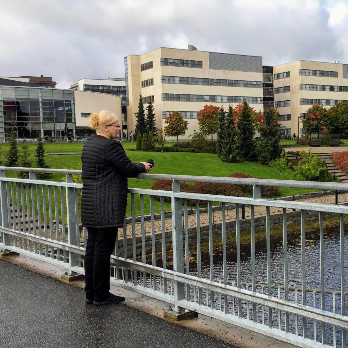 Aino Peltonen seisoo sillalla ja katsoo kauas mietteliäästi.