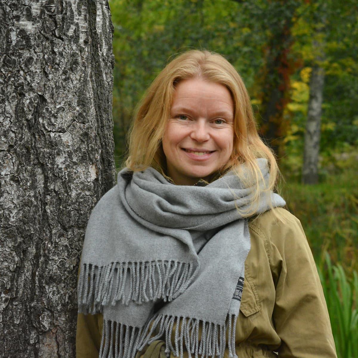 Mai Suominen seisoo puun vieressä.