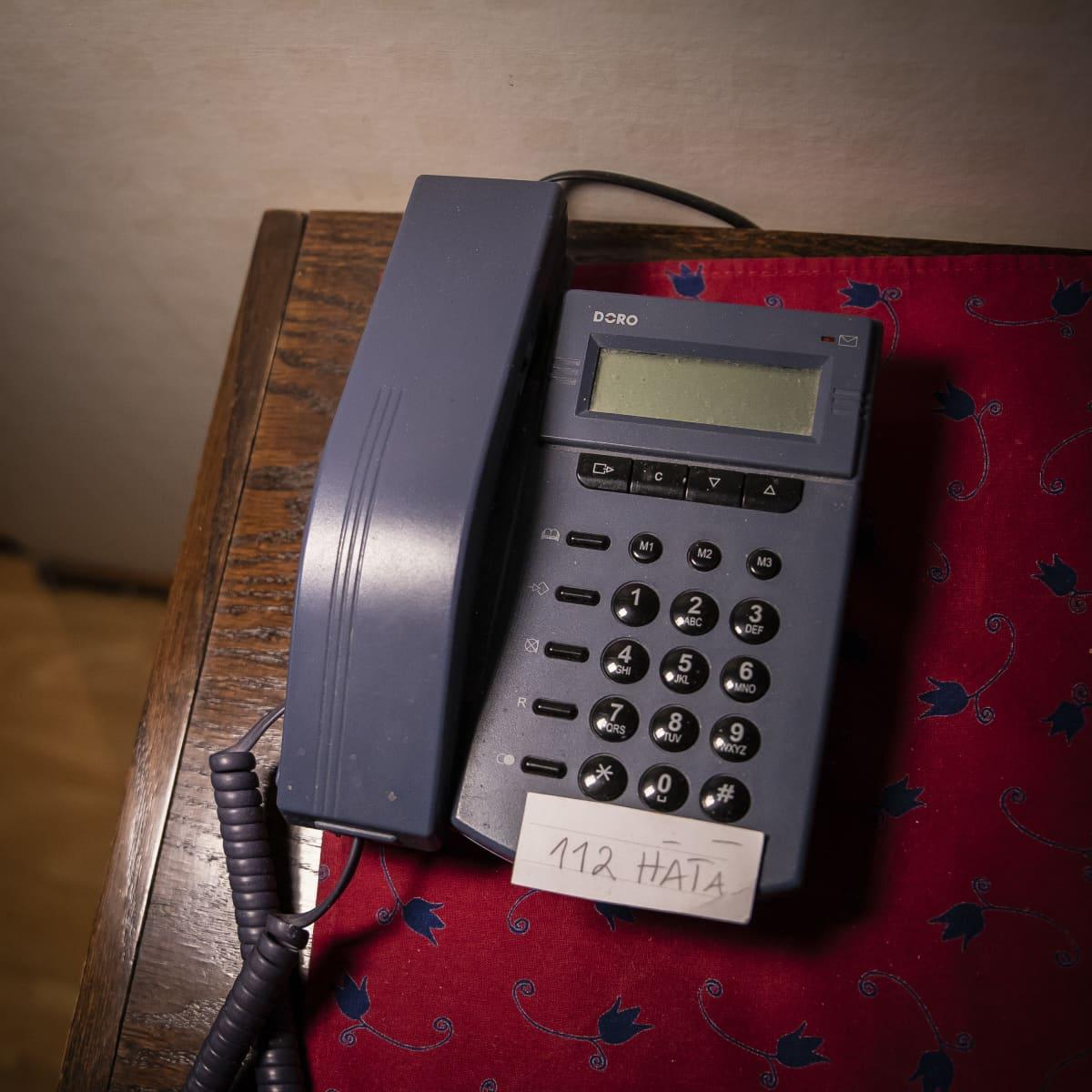 Puhelin, johon on merkitty lapulla hätänumero.