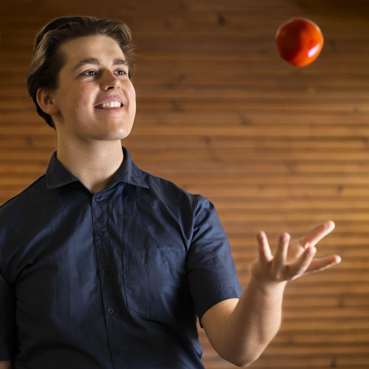 Antti Komulainen heittää tomaatin ilmaan.