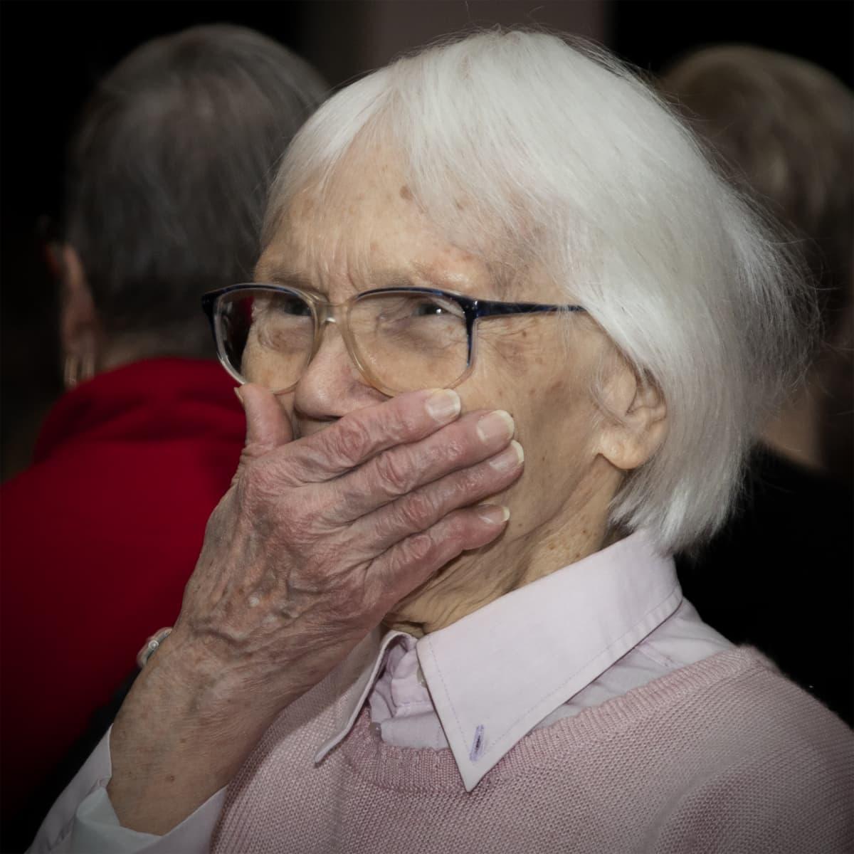 Anja Räsänen nauraa käsi suunsa edessä.