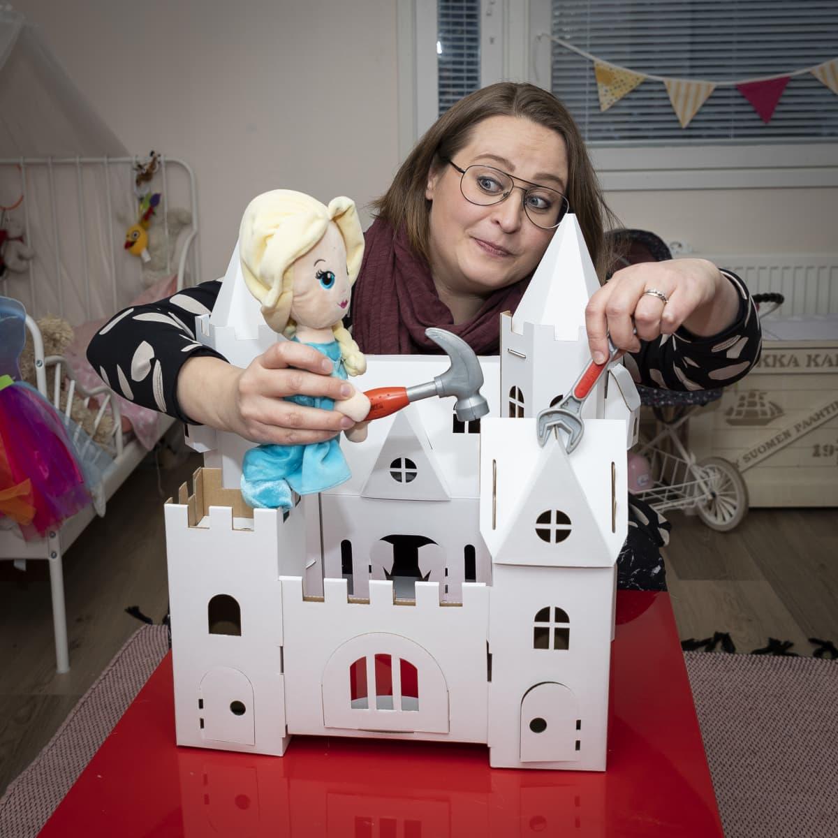 Lelulinnan vieressä oleva nainen pitelee Frozenin Elsa-nukkea kädessään. Elsalla on vasara kädessään.
