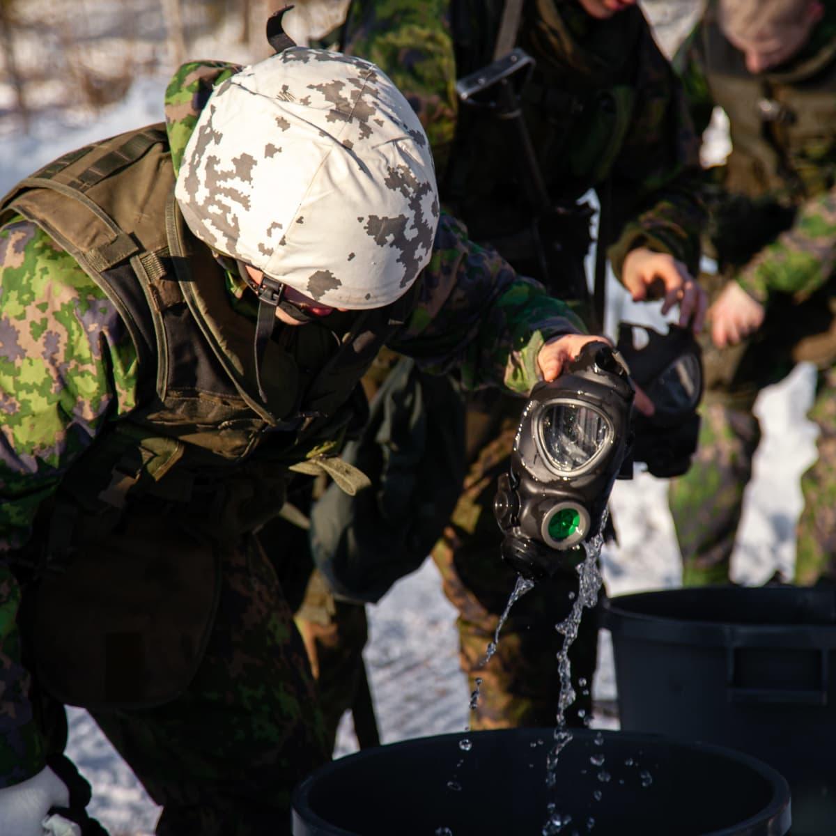 Sotilas pesee kaasunaamaria harjoituksen jälkeen.