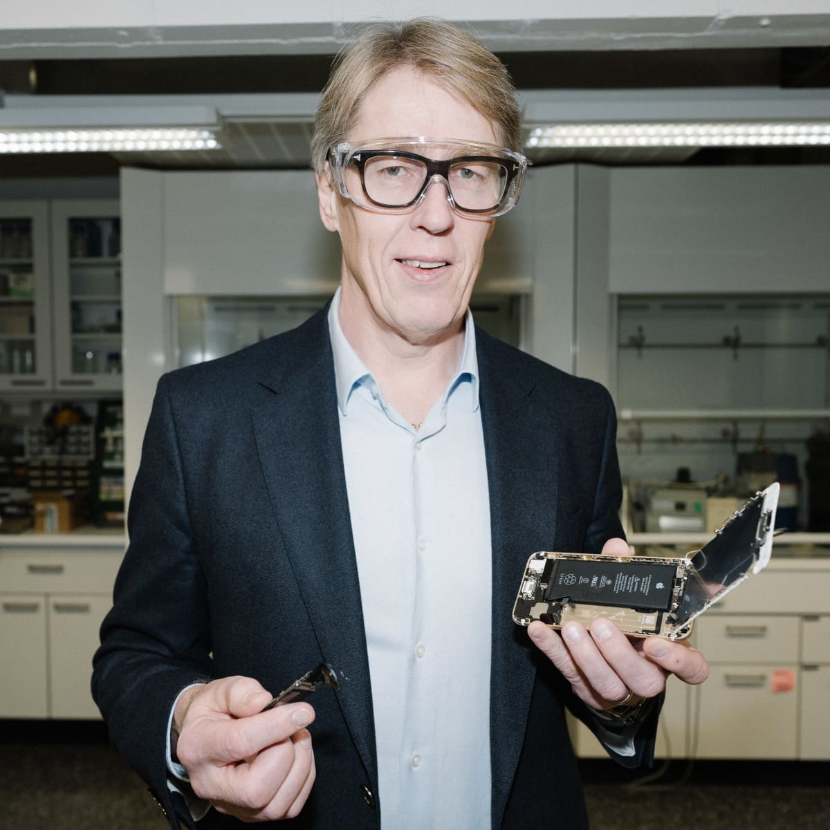 Professori Ari Jokilaakso pitää kädessään avattua älypuhelinta.