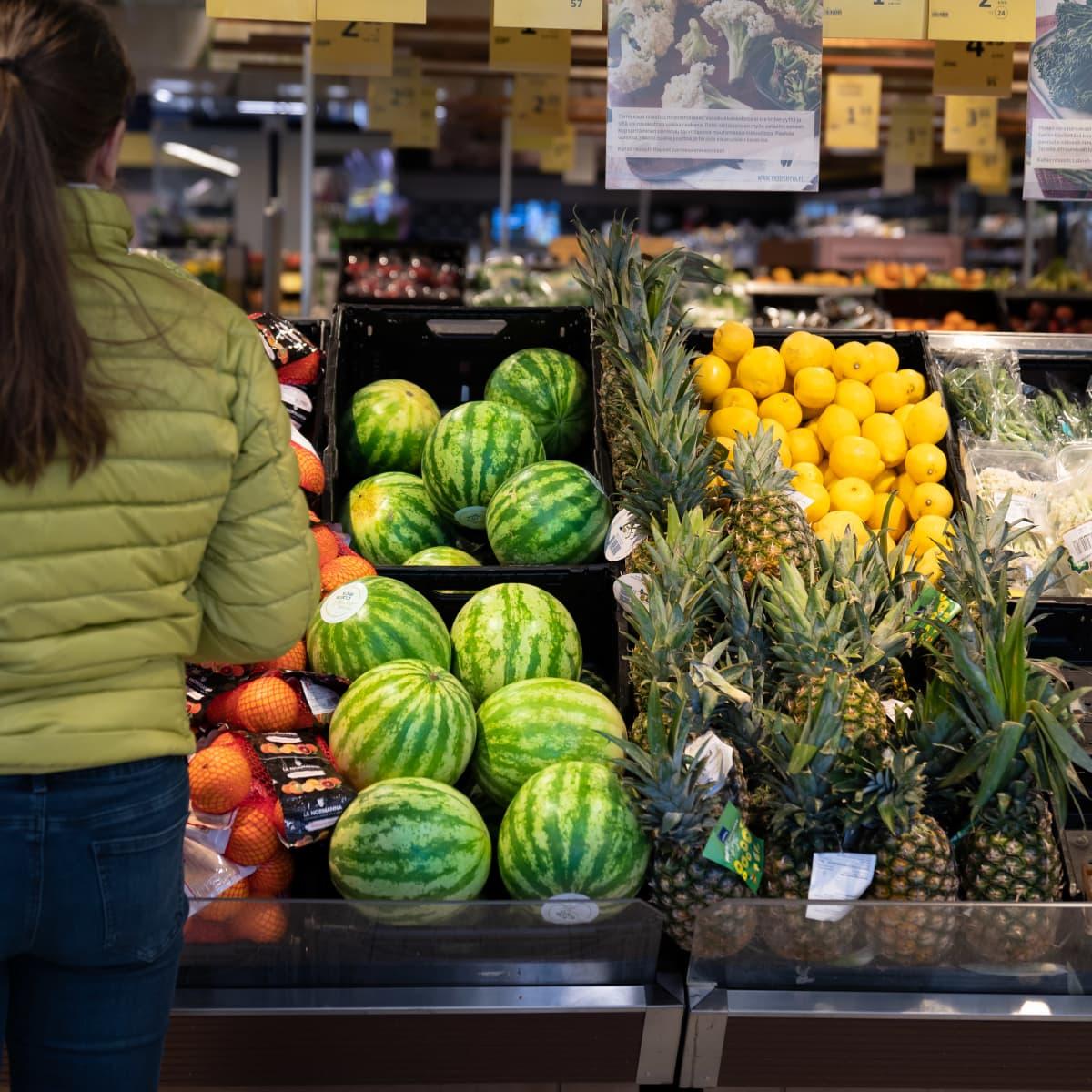 Anonyymi nainen ruokakaupan hedelmäosastolla valitsemassa tuotteita.