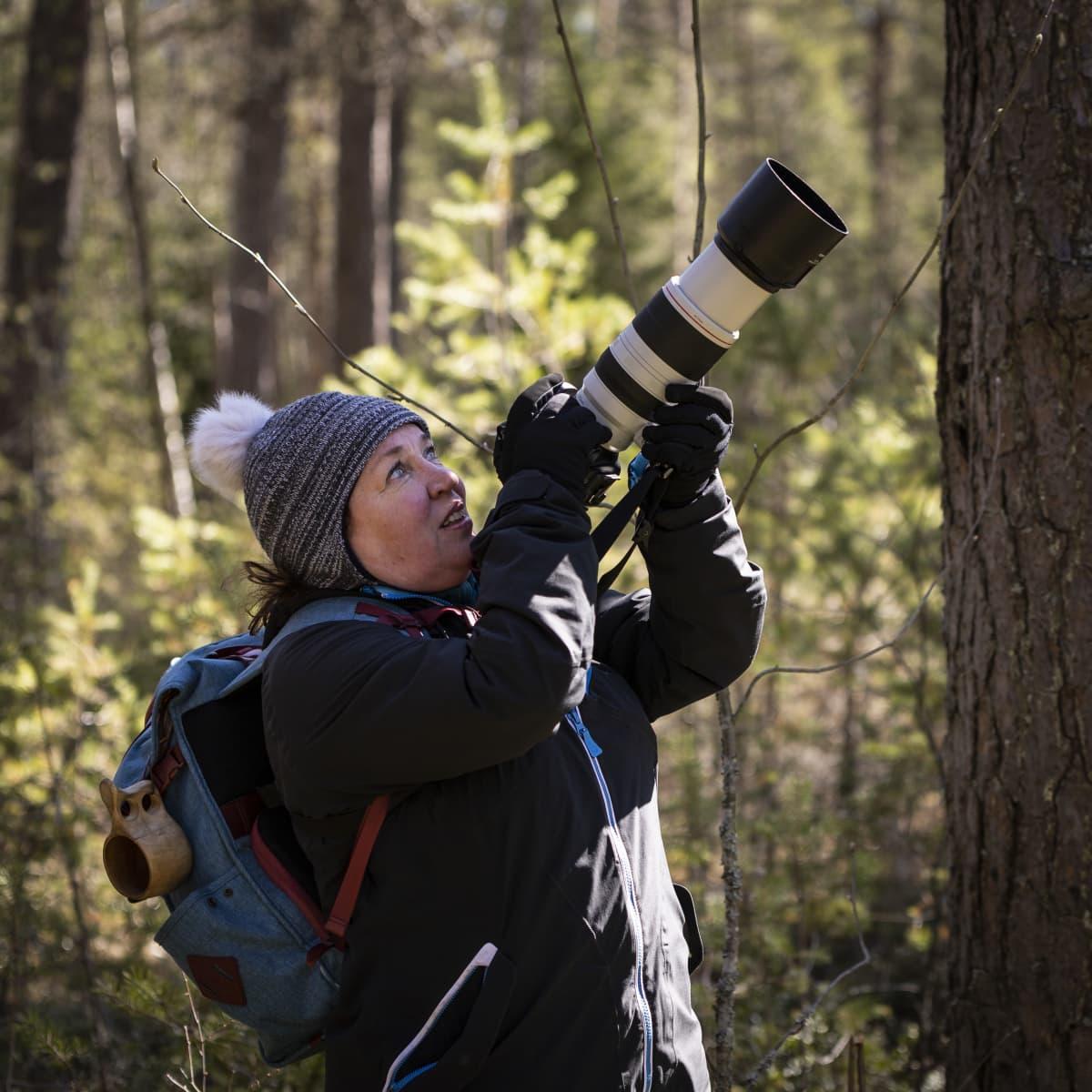 Anne Keski-Vinkka seisoo metsässä ja katsoo kameransa takaa ylös puihin.