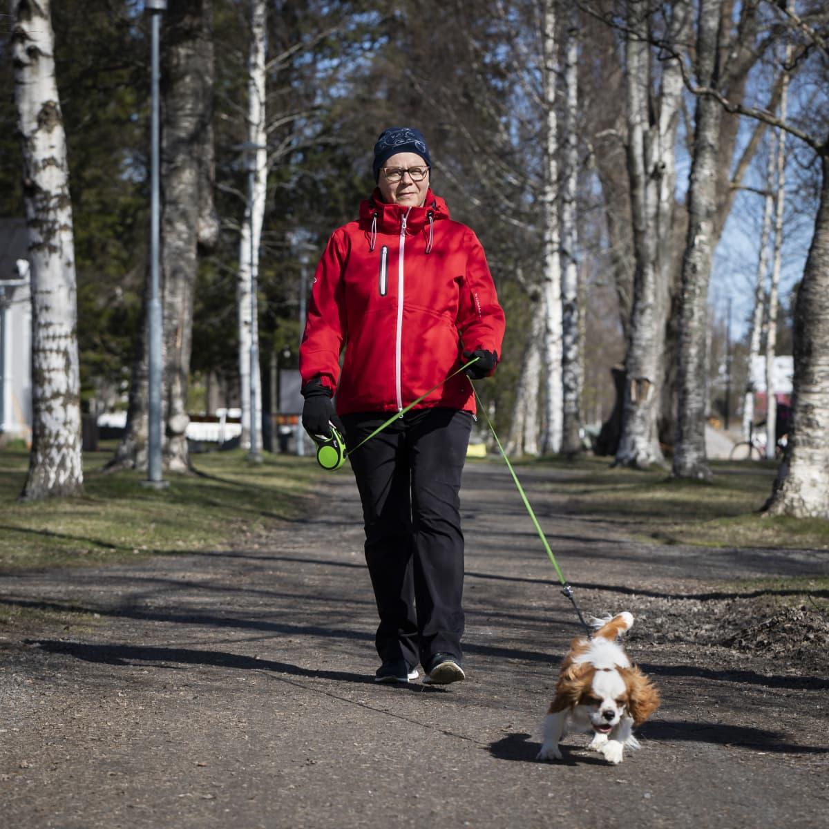 Pia Björkgren ulkoiluttaa koiraansa puistoalueella.