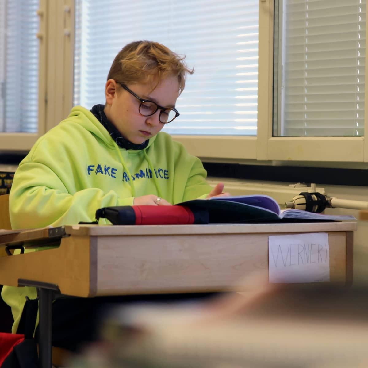 Silmälasipäinen Werneri Lappi istuu neonkeltainen huppari päällään pulpetissa ja tekee kirjasta tehtäviä. Pulpetin etuosassa on kyltti, jossa lukee Werneri.