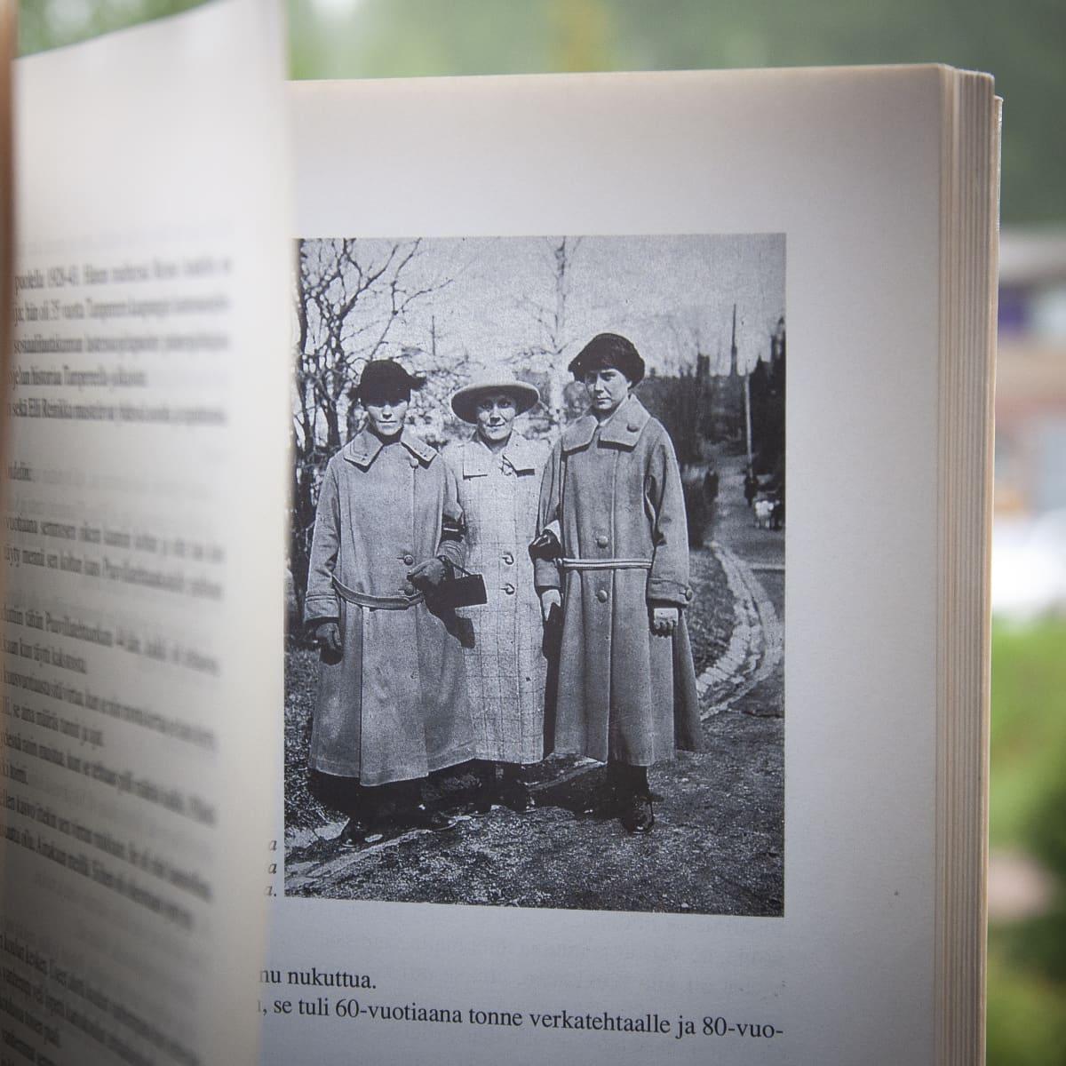 Kolme naista seisoo kadulla vierekkäin käsikynkässä, yllä pitkät päällystakit ja hatut.