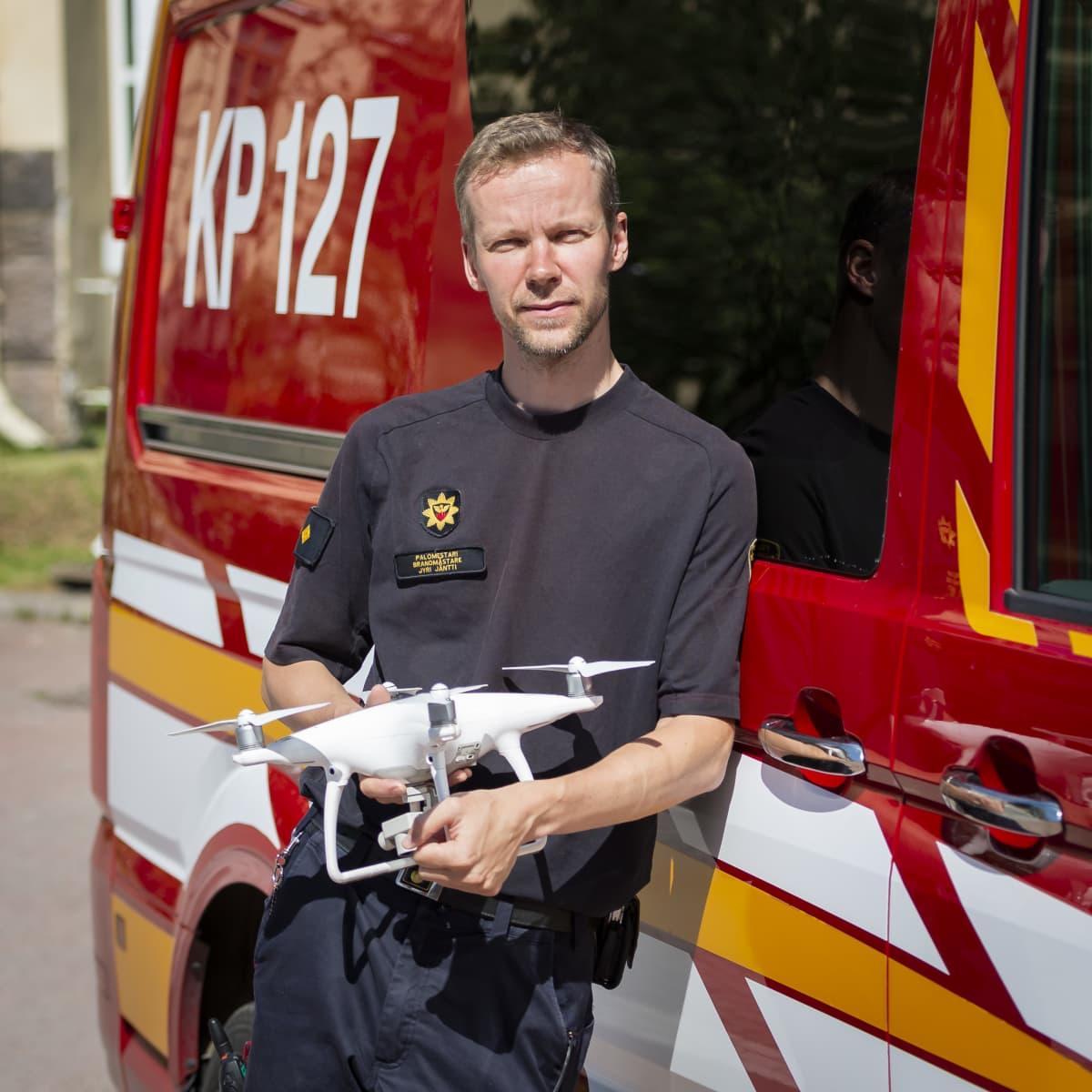 Jyri Jäntti nojaa paloautoon drooni käsissään.