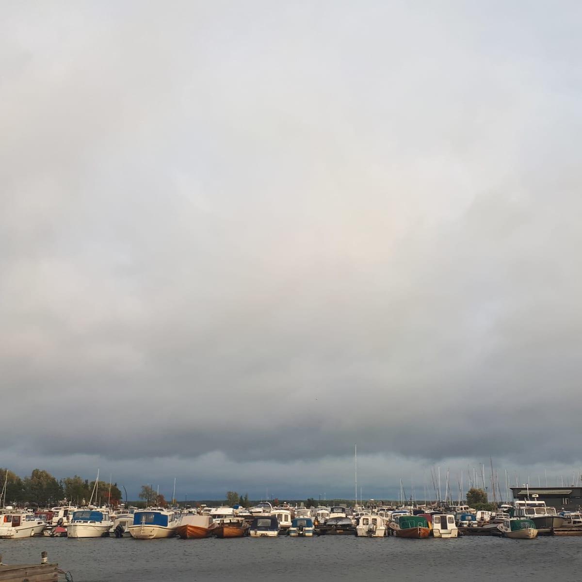 veneitä satamassa tumman taivaan alla