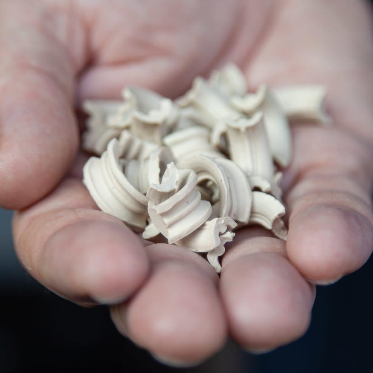 Kädessä valkoista mikrobipohjaisen EM-teknologian (Effective Micro-organisms) vedenpudistukseen tarkoitettua mikro-organismirouhetta.