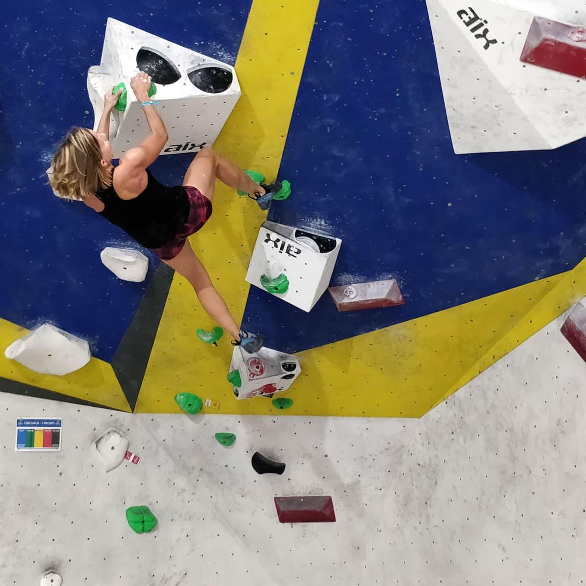 Jenni Christiansen kiipeää sisäkiipeilyhallin boulder-seinällä.