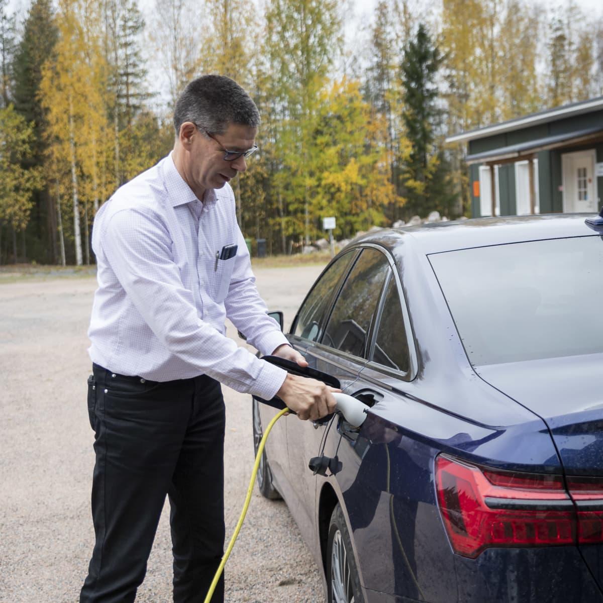 Hannu hautala laittaa latauspistokkeen sähköautoonsa.