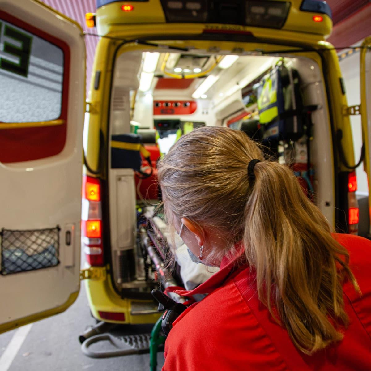 Ensihoitaja lastaamassa tyhjiä paareja ambulanssiin.