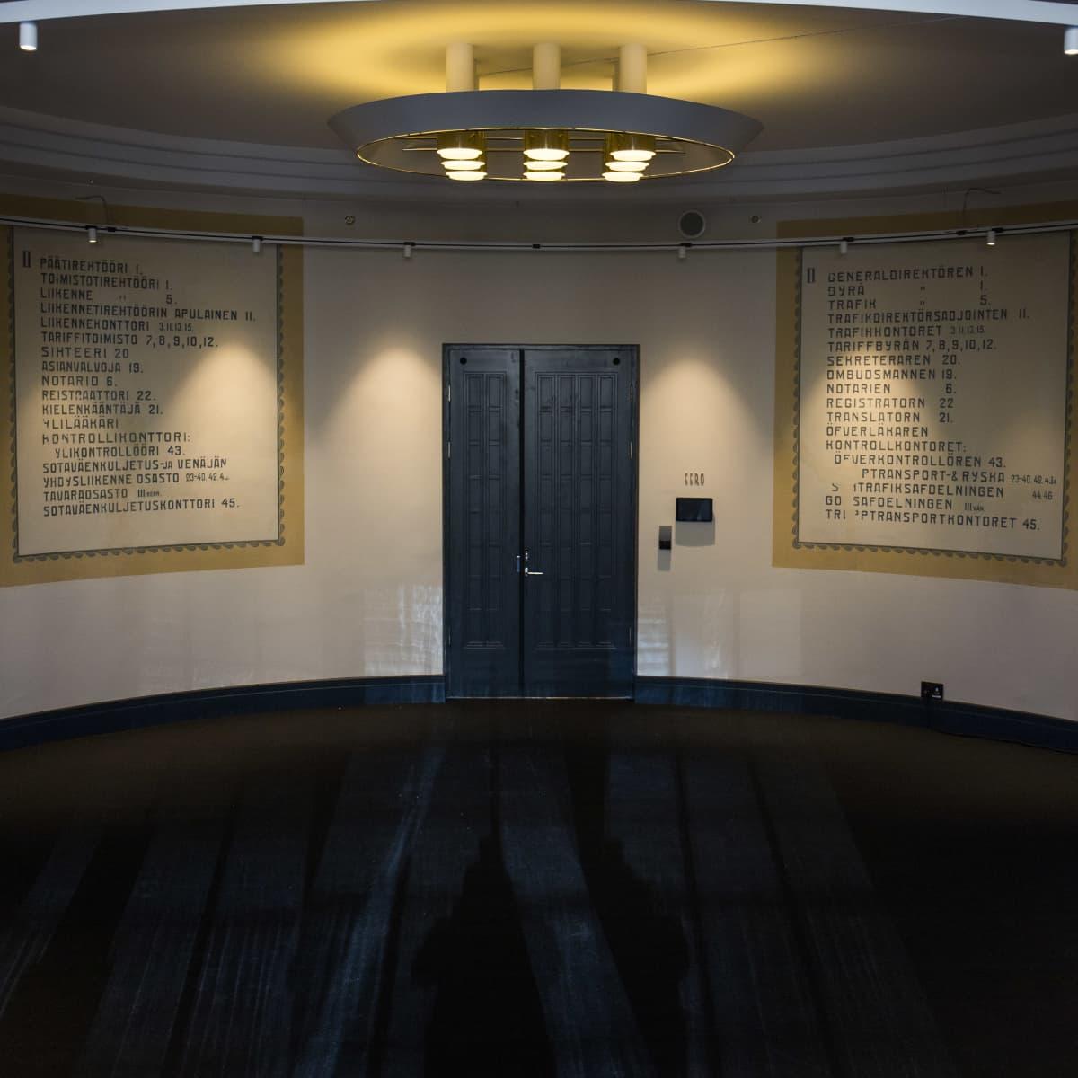 Scandic Grand Central Helsinki -hotellin käytävä, jossa näkyvillä vanha seinämaalaus, siinä kerroksessa työskennelleitä ammattinimikkeitä.