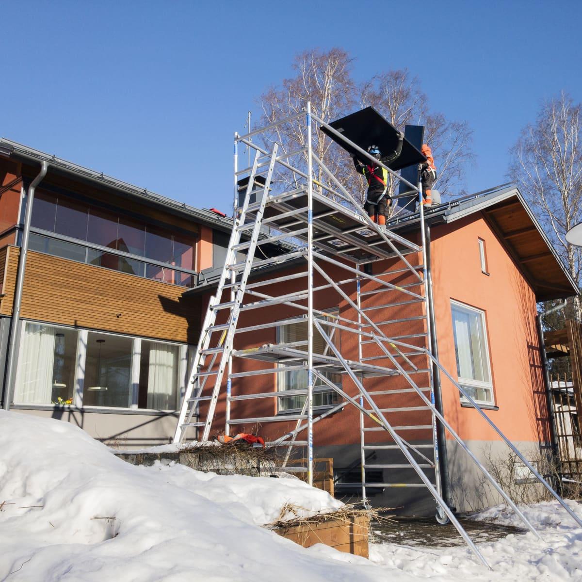 Aurinkopaneeleja nostetaan omakotitalon katolle.