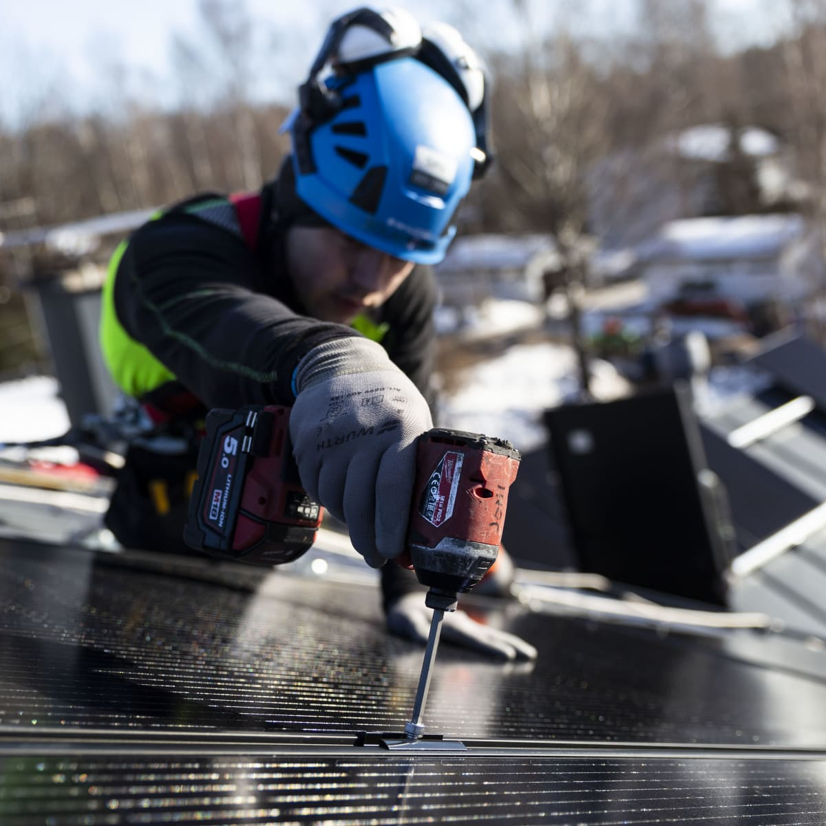 Solarvoima Oy:n asentaja Joni Särkinen asentaa aurinkopaneeleja omakotitalon katolle.