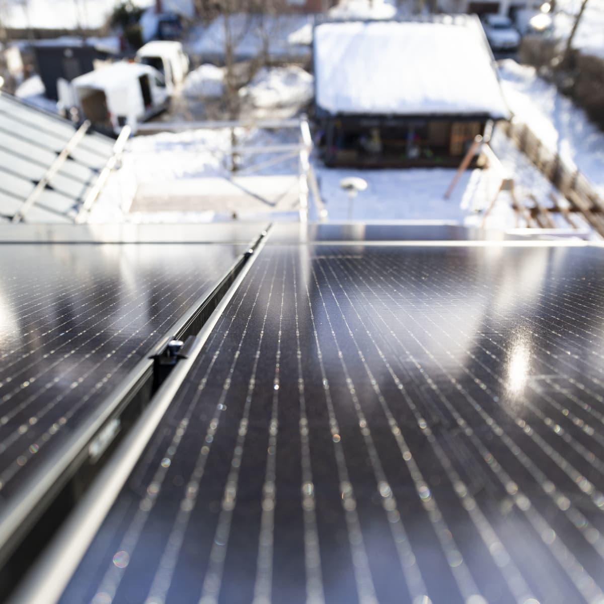 Aurinkopaneeleja omakotitalon katolla.