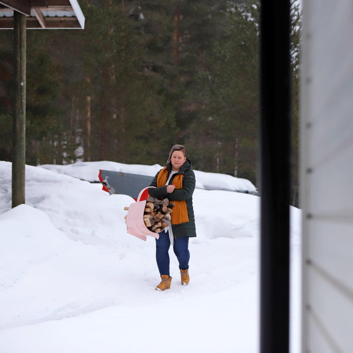 Juvalainen Anna-Mari Hangas-Tuovinen hakee polttopuita etätyöpäivänsä ohessa.
