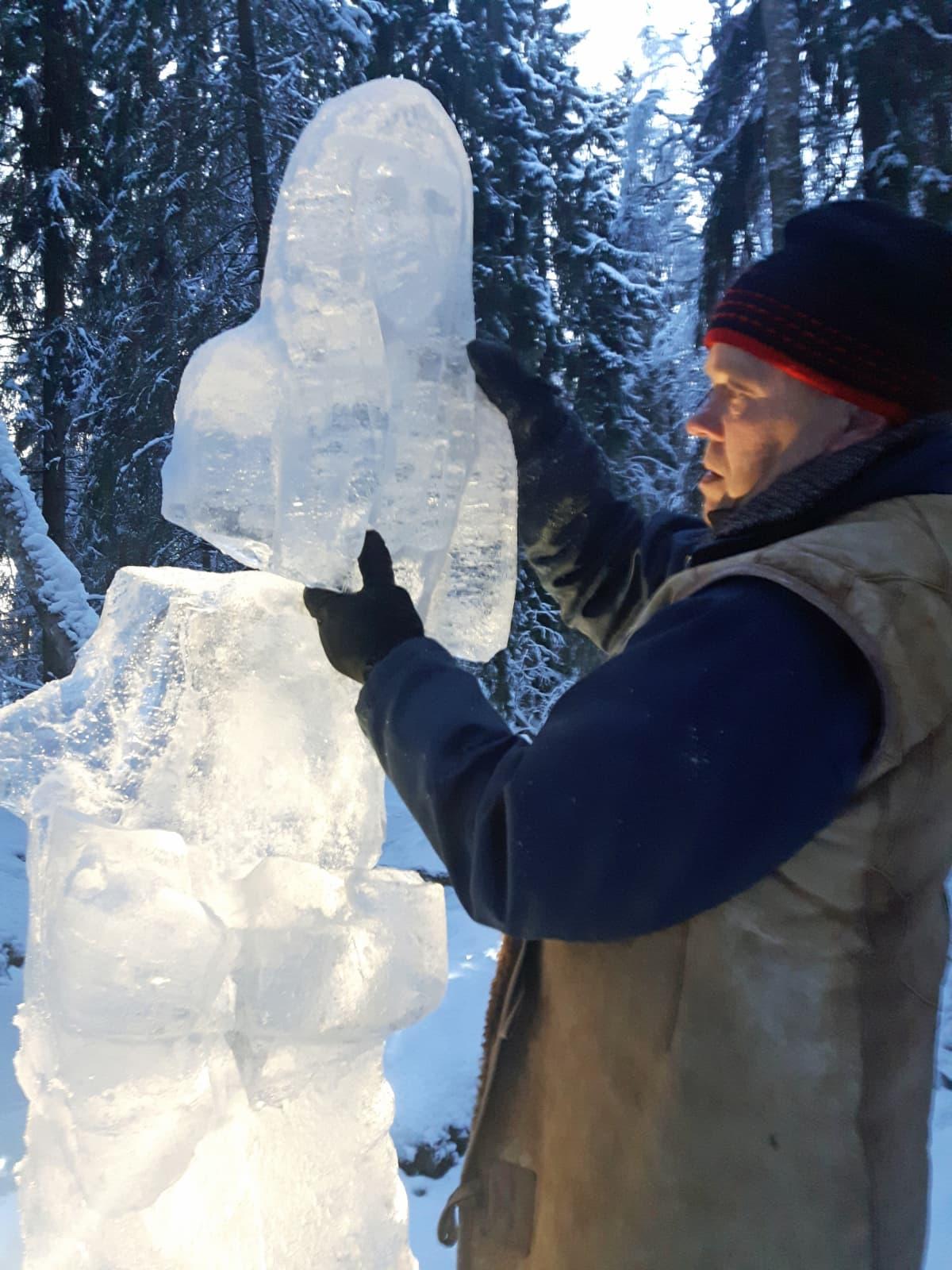 Mies nostaa irronnutta jääveistoksen osaa takaisin paikoilleen.