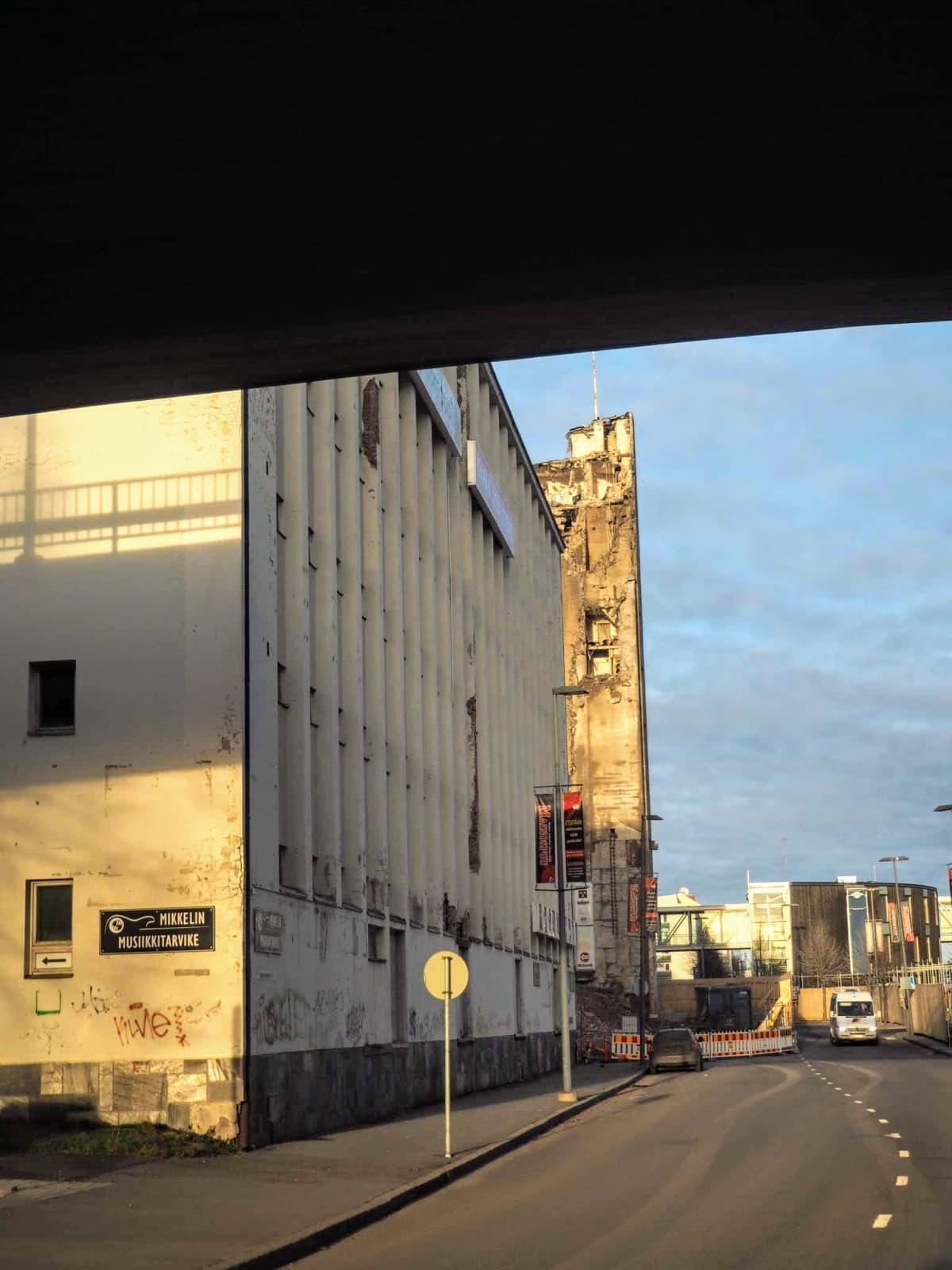 Kuva hieman ränsistyneestä Suomen Osuuskauppojen entisestä virastotalosta. Taustalla pilkistävät osittain puretut viljasiilot.