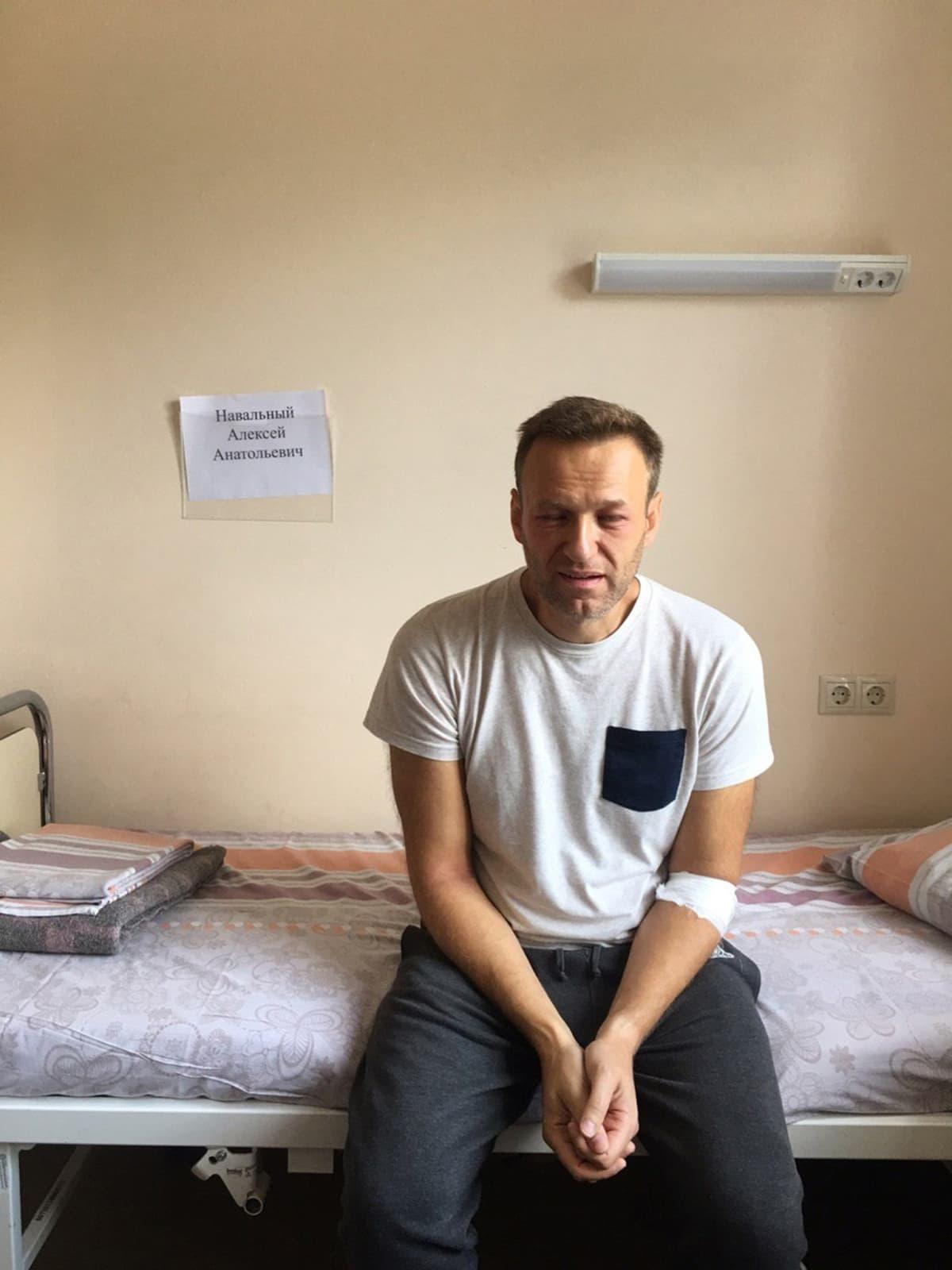 Aleksei Navalnyi istuu sängyllä.