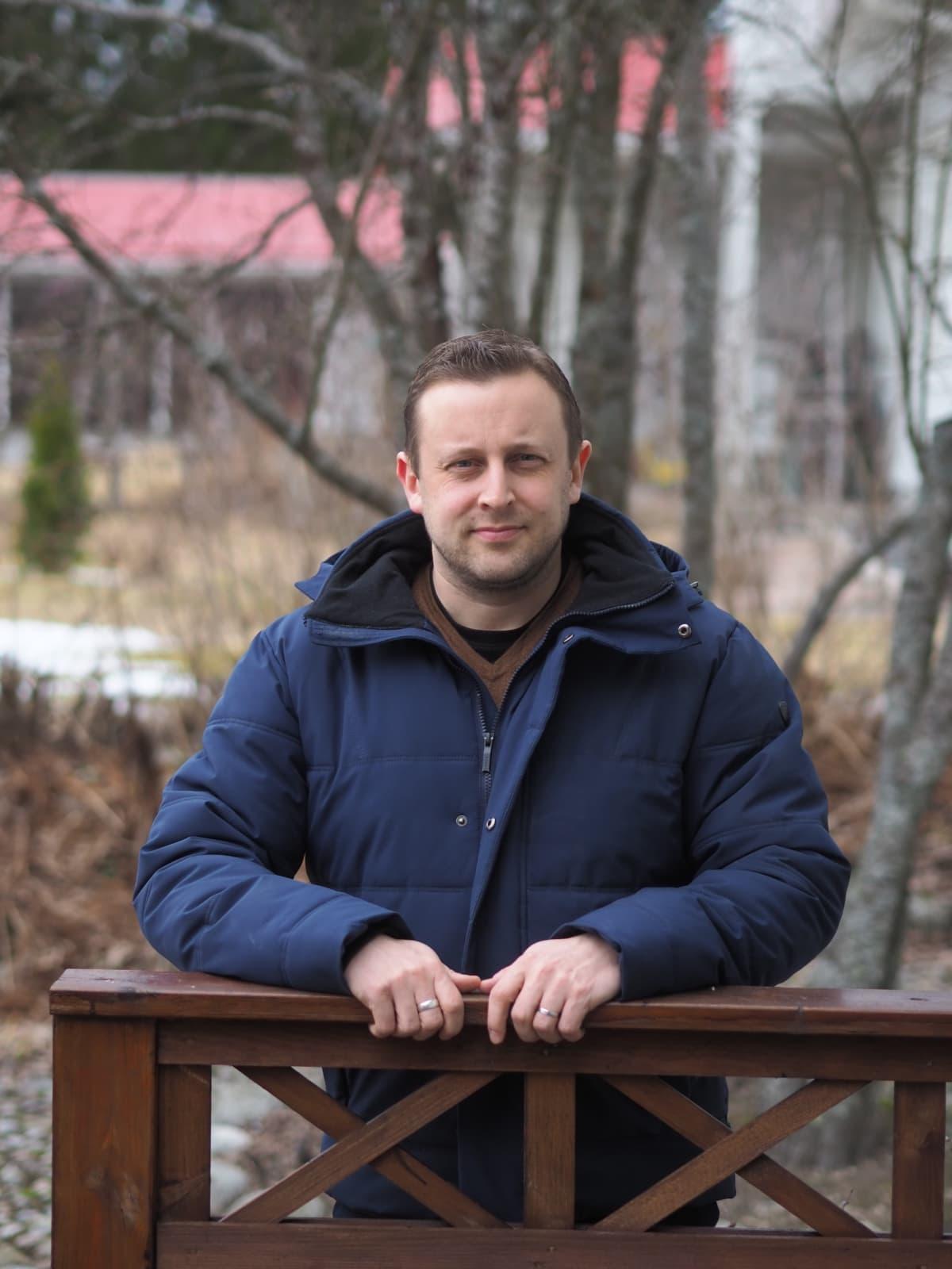 Valtio-opin dosentti Jouni Tilli nojaa puisen aidan kaiteeseen molemmilla käsillään, päällään tummansininen toppatakki. Taustalla syksyistä vesakkoa.