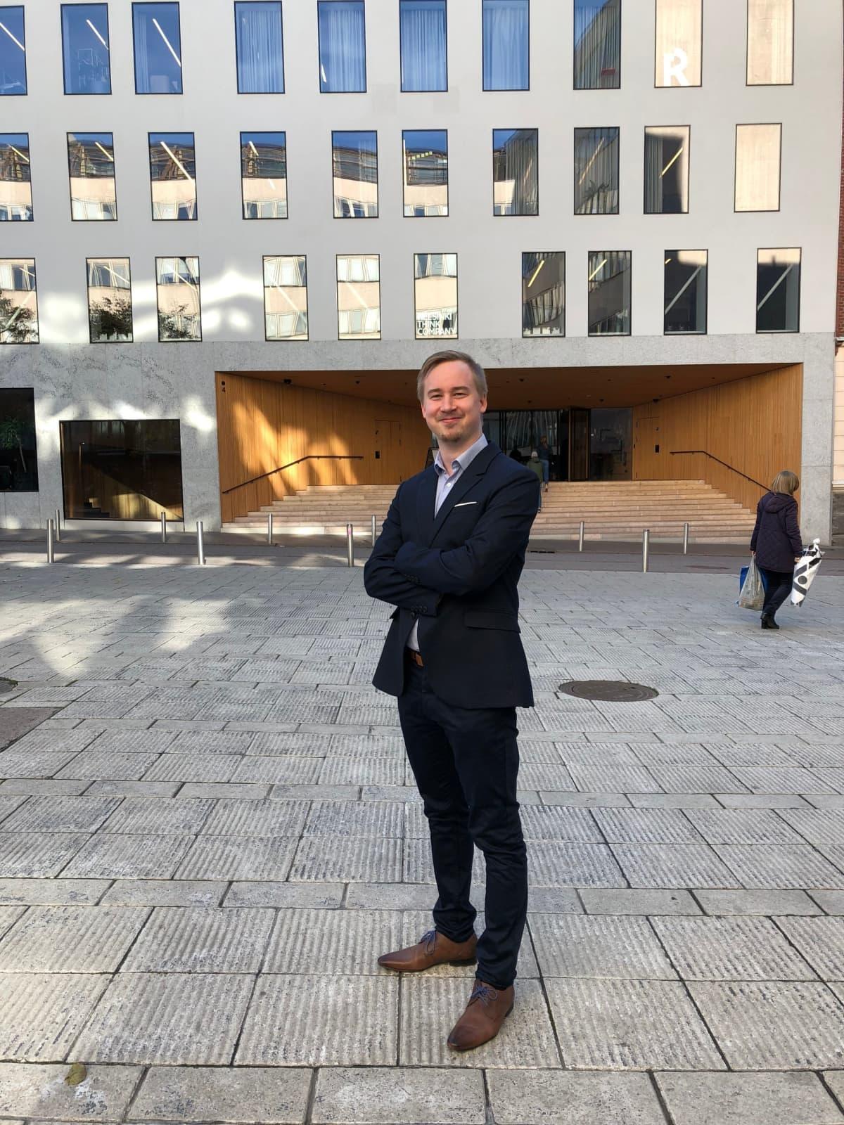 Juuso Lumilahti seisoo Helsingin oikeustieteellisen tiedekunnan edustalla.