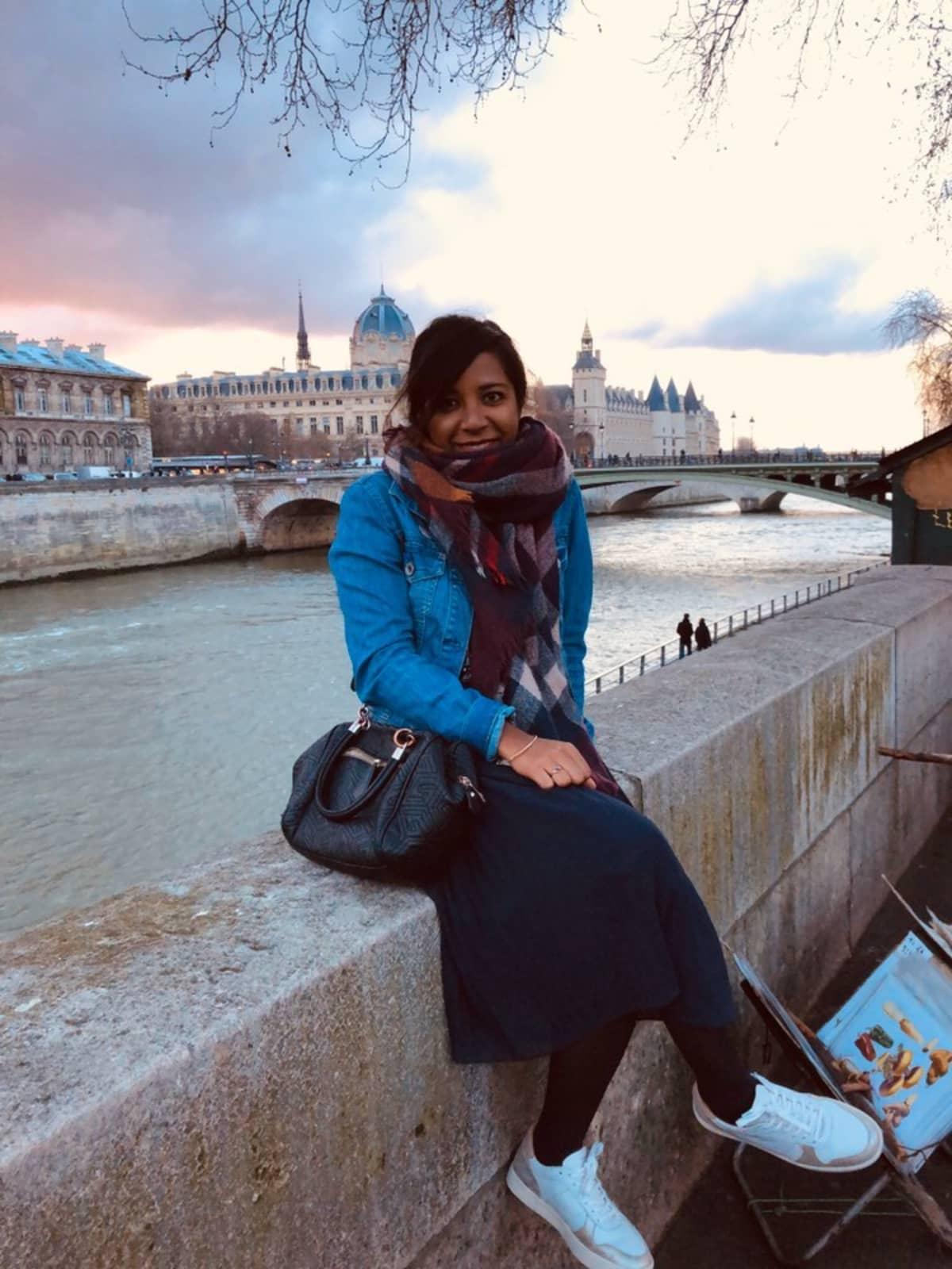 Priscilla Ravelojaona istuu Pariisissa Seine-joen edustalla