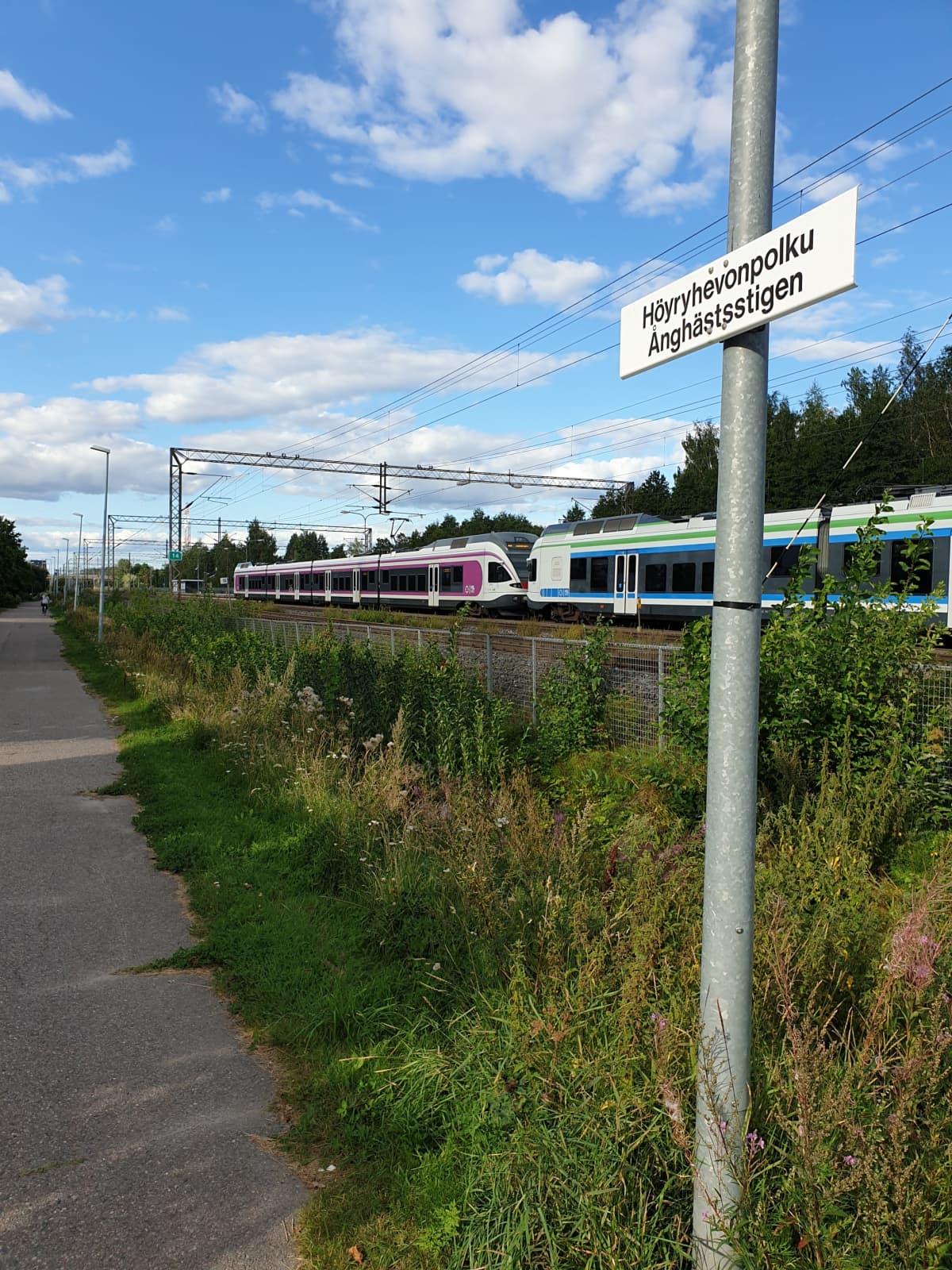 Katukyltti, jossa lukee Höyryhevonpolku. Taustalla junia.