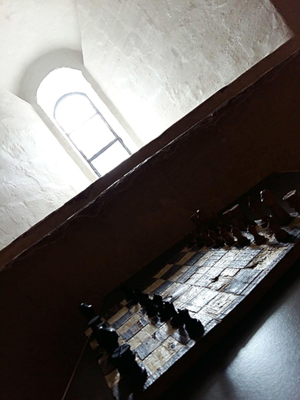 Puusta tehty shakkilauta keskiaikaisen linnan huoneen pöydällä
