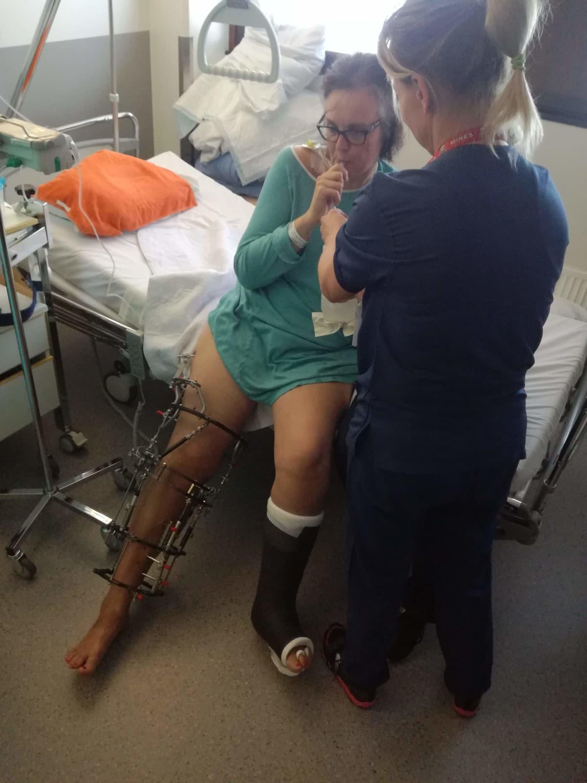 Hoitaja auttaa Maarit Talvitietä sairaalavuoteella.