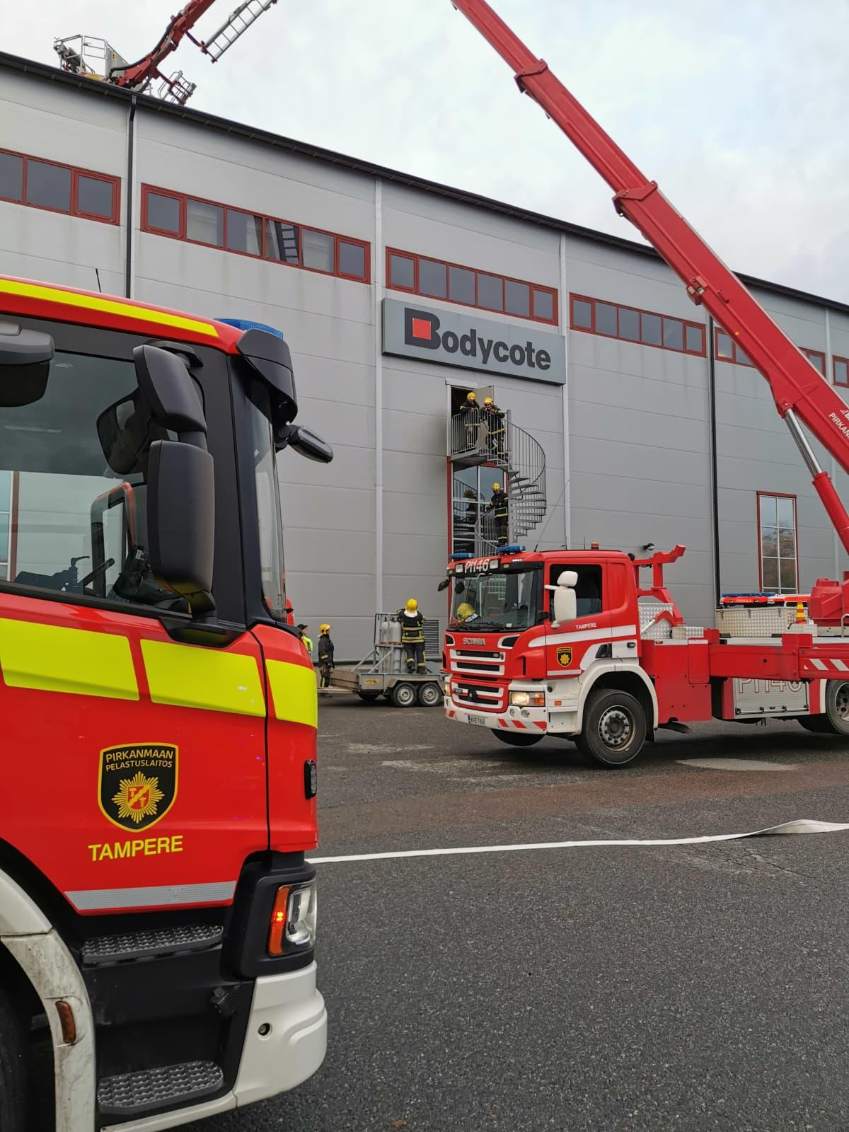 Palomiehiä ja paloautoja teollisuushallilla