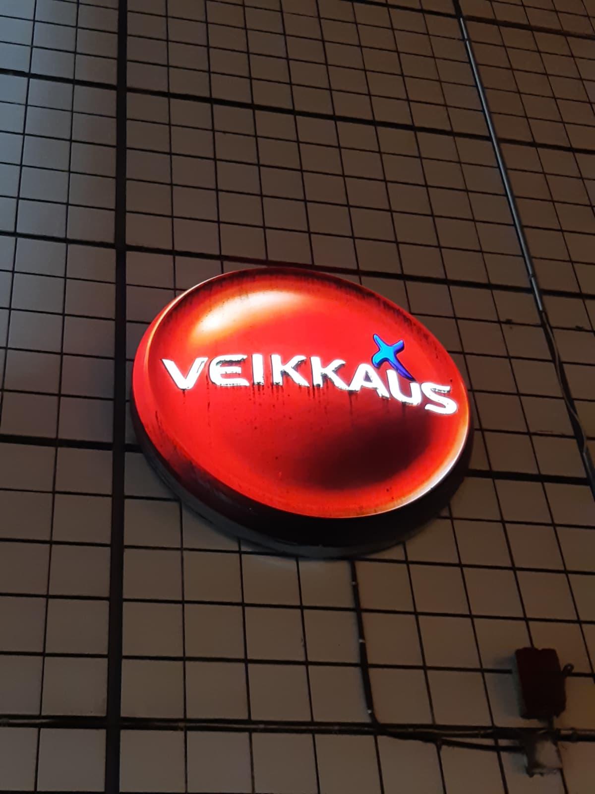 En upplyst Veikkaus-logo på en husvägg