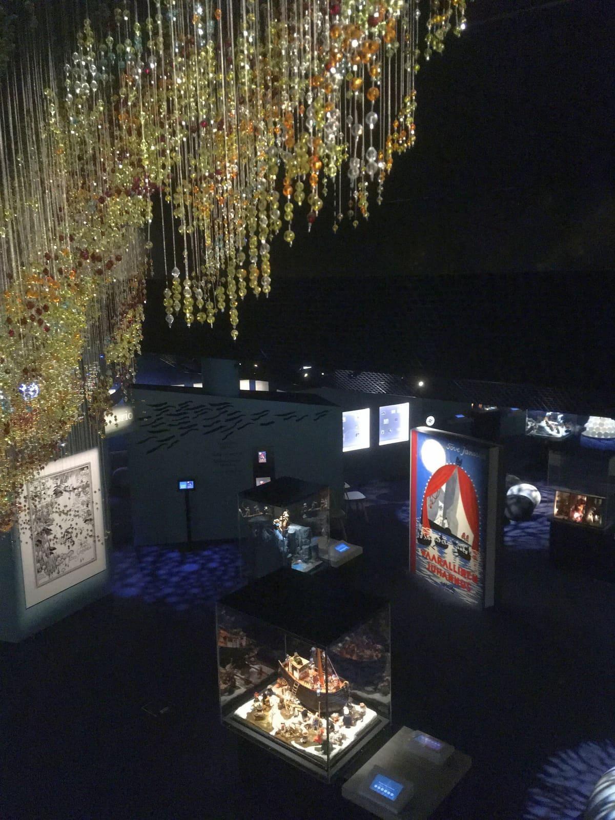 Näkymä Muumimuseon ylätasanteelta alas. Etualalla on pyrstötähteä esittävä helmiteos ja alhaalla näkyy pienoismaailmoja lasikuvuissaan.