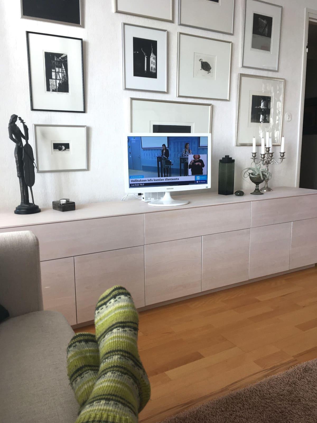 Aila Seppälä katselee hallituksen koronainfoa tv:stä.