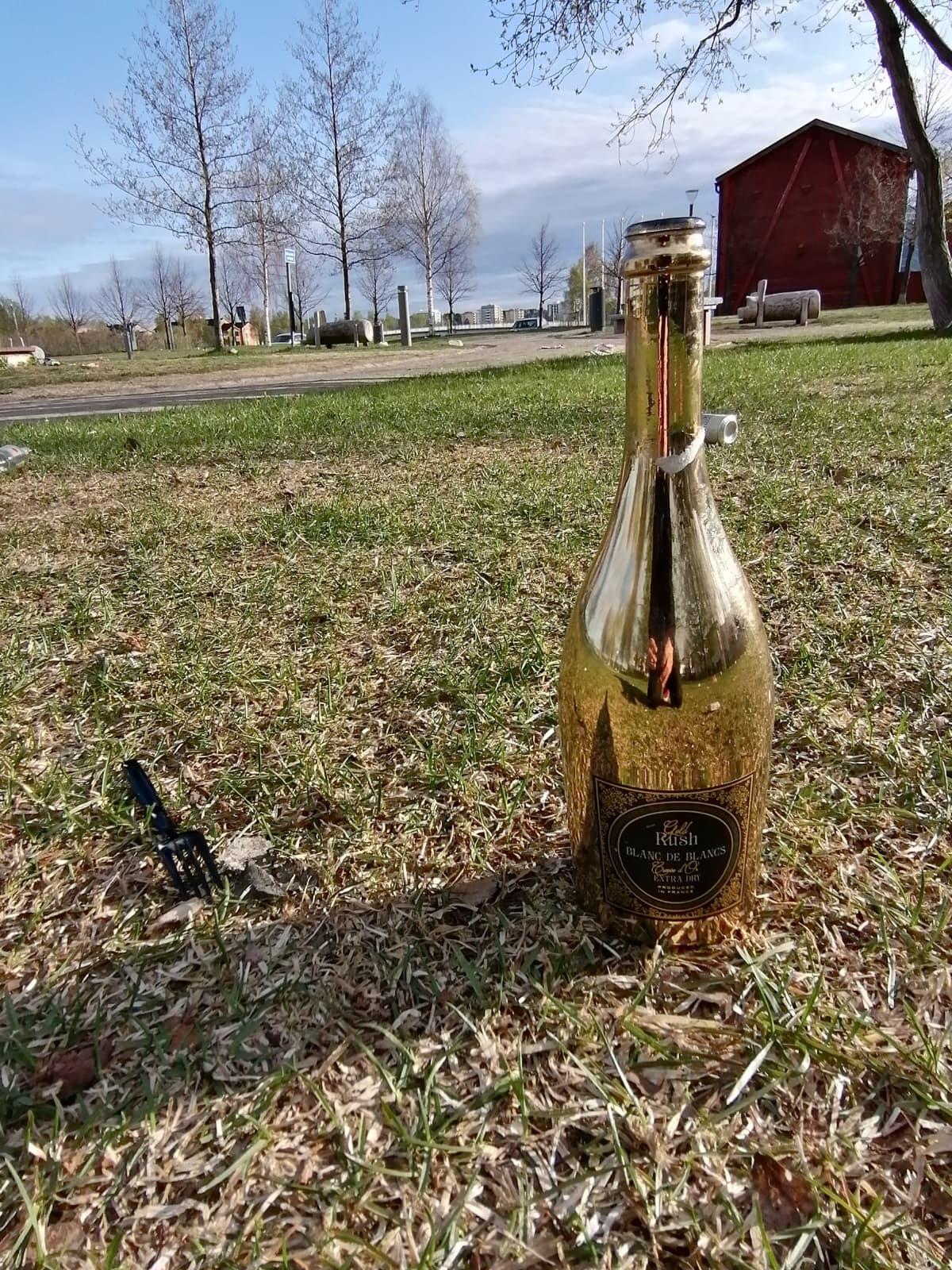Tyhjä samppanjapullo on jätetty Oulun Kiikeliin.