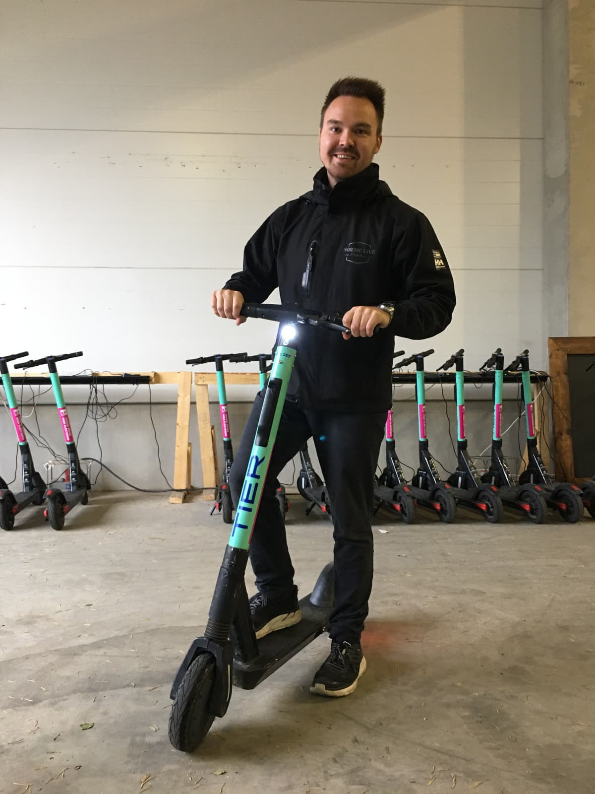 Tommi Mäki nojaa sähköpotkulautaan varastotiloissa Vaasassa