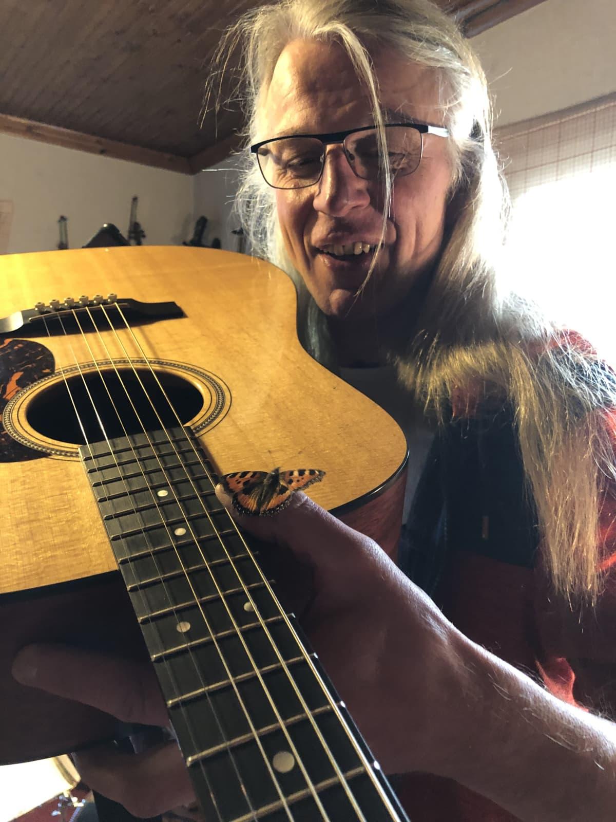 Hannu Sepponen ja marraskuinen perhonen sormella, joka pitelee kitaraa.