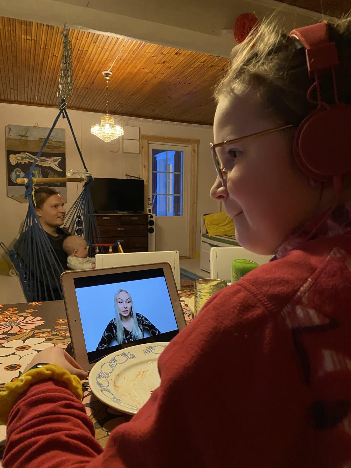 Milli katsoo tabletilta tubettajaa. Takana näkyvät isä-Antti ja Aatos-vauva.