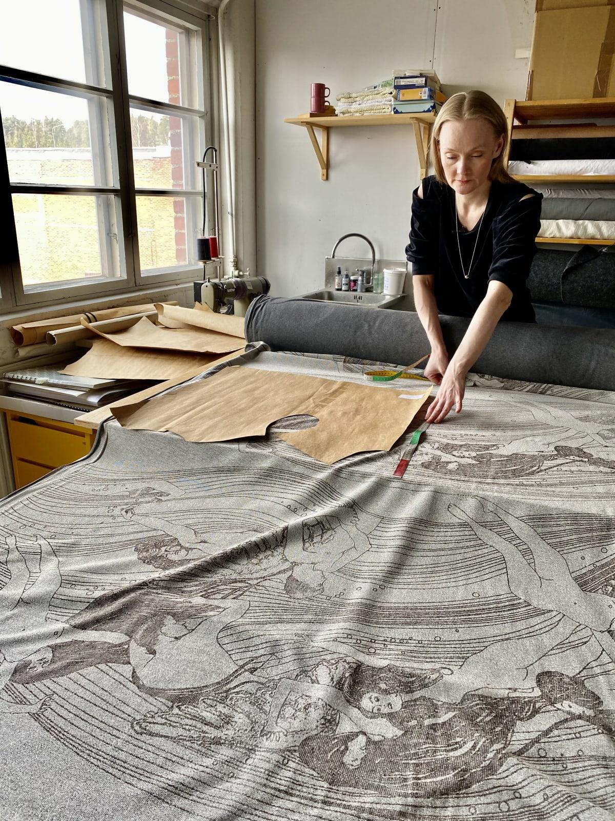 Vaatesuunnitelija Marjut Uotila tutkii työpöydälleen auki levitettyä kangasta.