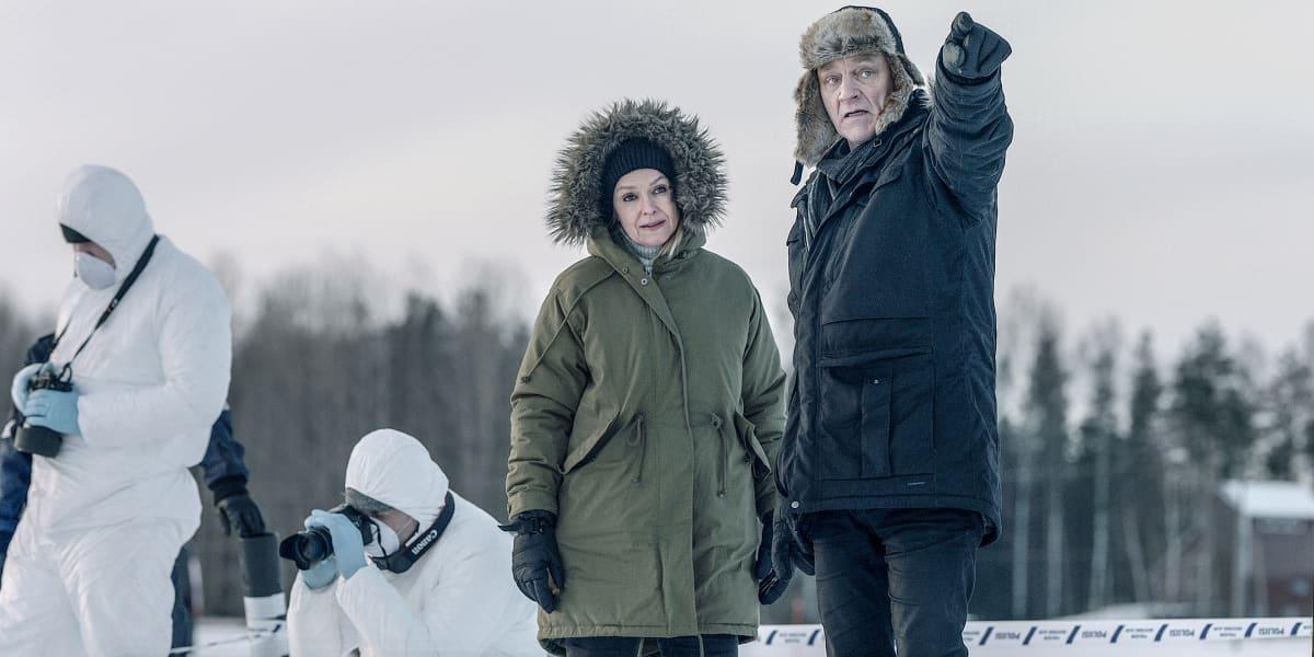 Sorjonen (Ville Virtanen) osoittaa sormella kuvan ulkopuolelle. Lena Jaakkola (Anu Sinisalo) katsoo sormen osoittamaan suuntaan, taustalla rikospaikkatutkijoita valkoisissa puvuissaan.