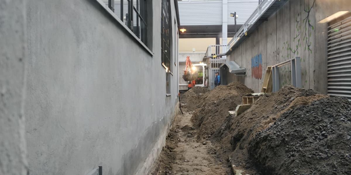 Kaivinkone työskentelee Valtiontalon seinän vierustalla ja kasaa maata pois seinän vierestä
