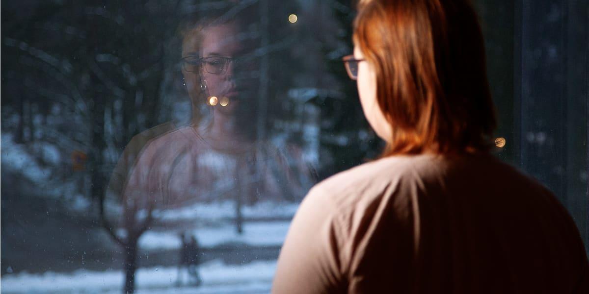 Nuori nainen katsoo ikkunasta.