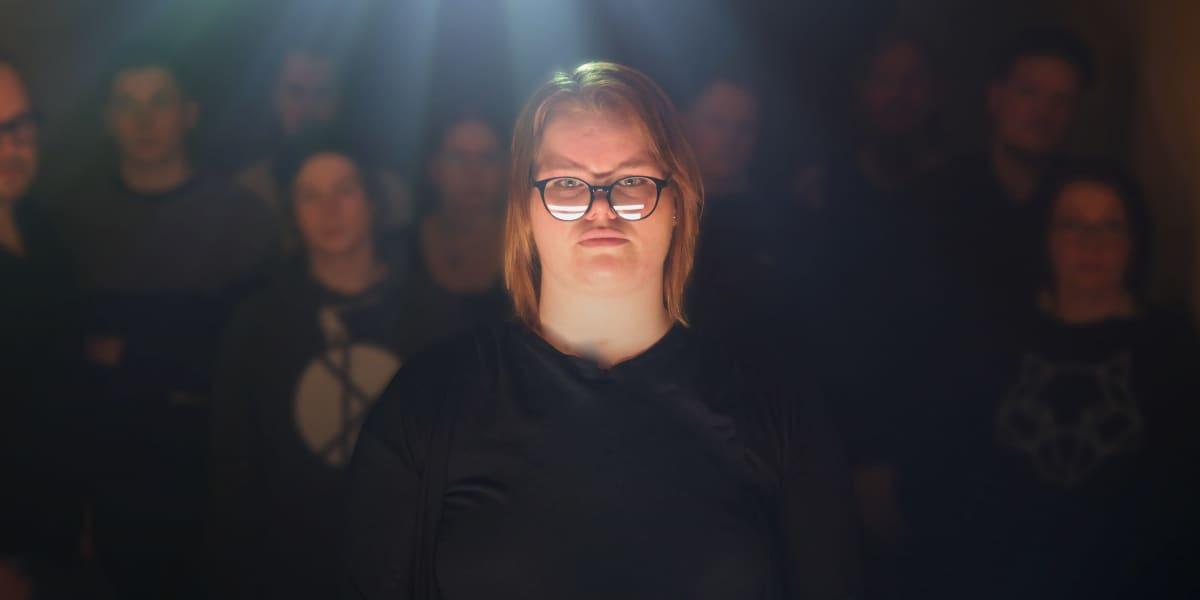 Nainen katsoo kohti kameraa ja taustalla on muita ihmisiä.