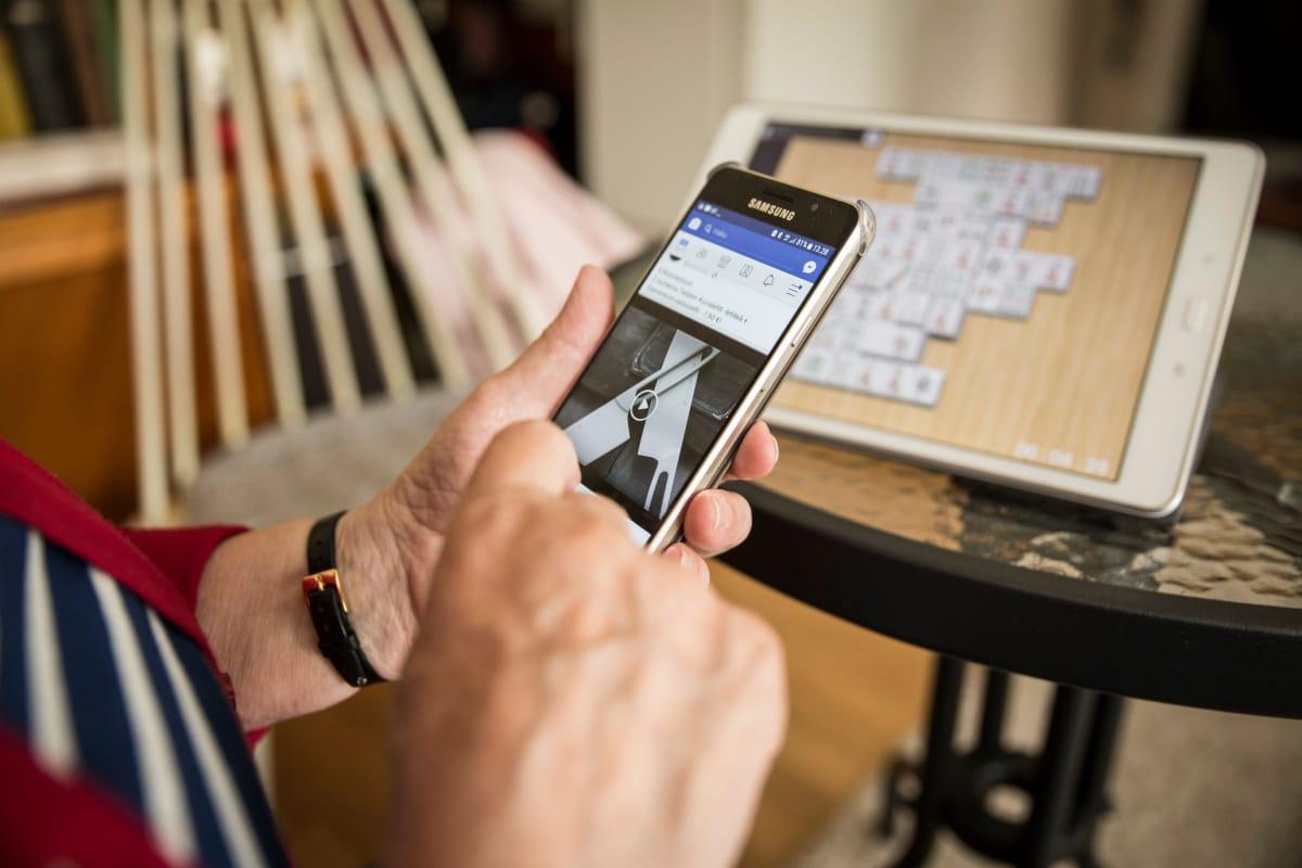 Maija Frantsi laittaa nettiyhteyden päälle kännykästä.